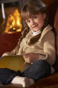 Young Girl Sitting On Sofa And Reading Book By Cosy Log Fire Stock Photos