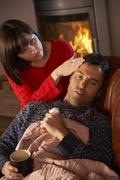 Wife Nursing Sick Husband With Cold Resting On Sofa By Cosy Log Fire Stock Photos