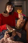 Wife Nursing Sick Husband With Cold Resting On Sofa By Cosy Log Fire - stock photo