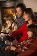 Family Relaxing Watching TV By Cosy Log Fire Stock Photos