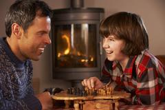 Father And Son Playing Chess By Cosy Log Fire Stock Photos