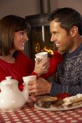 Couple Enjoying Tea And Cake By Cosy Log Fire Stock Photos