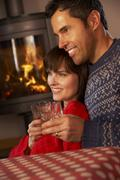 Middle Aged Couple Sitting On Sofa Watching TV By Cosy Log Fire - stock photo