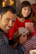 Couple Playing Cards By Cosy Log Fire Stock Photos