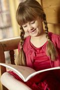Young Girl Sitting On Wooden Seat Reading Book - stock photo