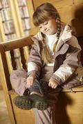 Young Girl Sitting On Wooden Seat Putting On Warm Outdoor Clothes And Boots - stock photo