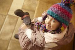 Young Girl Sitting On Wooden Seat Putting On Warm Outdoor Clothes And Boots Stock Photos