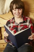 Young Boy Sitting On Wooden Seat Reading Book - stock photo