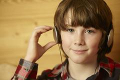 Young Boy Sitting On Wooden Seat Listening To MP3 Player - stock photo