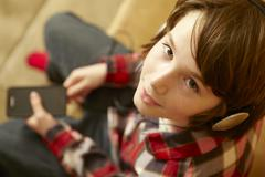 Young Boy Sitting On Wooden Seat Listening To MP3 Player Stock Photos