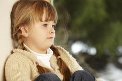 Young Girl Sitting On Window Ledge Looking At Snowy View Stock Photos