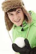 Teenage Boy Holding Snowball Wearing Fur Hat - stock photo
