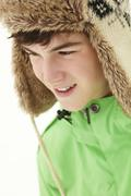 Portrait Of Teenage Boy In Snow Wearing Fur Hat Stock Photos