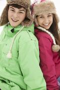 Stock Photo of Portrait Of Teenage Couple In Snow Wearing Fur Hats