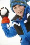 Young Boy About To Throw Snowball Wearing Woolly Hat - stock photo