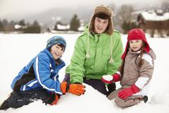 Group Of Children Building Snowman Wearing Woolly Hats Stock Photos