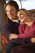 Middle Aged Couple Chatting On Sofa In Chalet With Winter View - stock photo