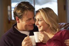 Middle Aged Couple Sitting On Sofa With Hot Drinks Stock Photos