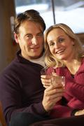 Middle Aged Couple Sitting On Sofa With Glasses Of Whisky - stock photo