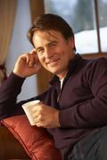 Middle Aged Man Relaxing With Hot Drink On Sofa Stock Photos