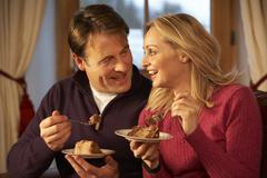 Couple Enjoying Slice Of Cake Sitting On Sofa Stock Photos
