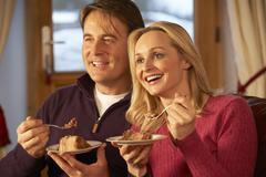 Couple Enjoying Slice Of Cake Sitting On Sofa Watching TV Stock Photos