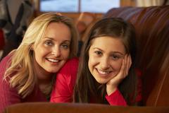 Portrait Of Mother And Daughter Relaxing On Sofa Together - stock photo