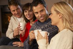 Group Of Middle Aged Couples Sitting On Sofa With Hot Drinks Talking - stock photo