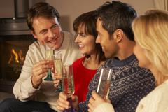 Group Of Middle Aged Couples Sitting On Sofa With Champagne - stock photo