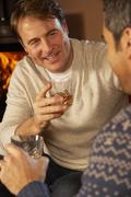 Two Middle Aged Men Relaxing Sitting On Sofa Drinking Whisky Stock Photos