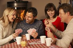 Group Of Middle Aged Couples Playing Cards Together - stock photo