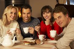 Group Of Middle Aged Couples Enjoying Tea And Cake Together - stock photo