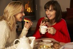 Two Middle Aged Women Enjoying Tea And Cake Together - stock photo