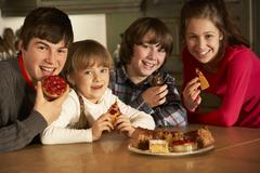 Group Of Children Enjoying Plate Of Cakes In Kitchen - stock photo
