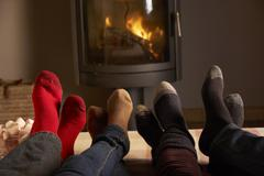 Close Up Of Familys Feet Relaxing By Cosy Log Fire With Marshmallows Stock Photos