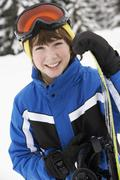 Young Boy With Snowboard On Ski Holiday In Mountains - stock photo