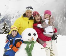 Family Building Snowman On Ski Holiday In Mountains Stock Photos