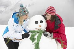 Stock Photo of Two Female Friends Building Snowman On Ski Holiday In Mountains