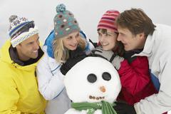 Group Of Friends Building Snowman On Ski Holiday In Mountains Stock Photos