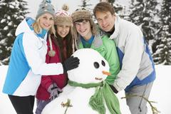 Stock Photo of Teenage Family Building Snowman On Ski Holiday In Mountains