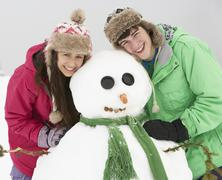 Two Teenagers Building Snowman On Ski Holiday In Mountains - stock photo