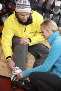 Sales Assistant Helping Man To Try On Ski Boots In Hire Shop Stock Photos