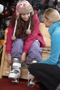 Sales Assistant Helping Teenage Girl To Try On Ski Boots In Hire Shop Stock Photos