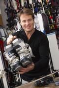 Sales Assistant With Ski Boots In Hire Shop Stock Photos