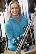 Female Sales Assistant With Skis In Hire Shop Stock Photos