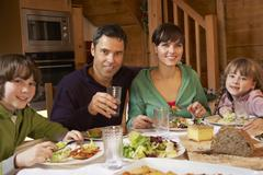 Family Enjoying Meal In Alpine Chalet Together Stock Photos