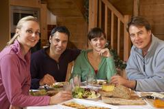Group Of Friends Enjoying Meal In Alpine Chalet Together Stock Photos