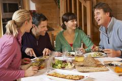 Group Of Friends Enjoying Meal In Alpine Chalet Together - stock photo