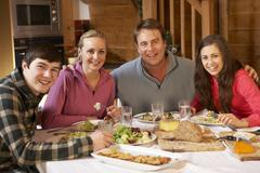 Teenage Family Enjoying Meal In Alpine Chalet Together Stock Photos