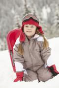 Young Girl Playing In Snow With Sledge On Ski Holiday In Mountains - stock photo